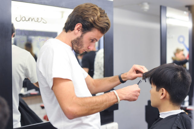 Student cutting a clients hair